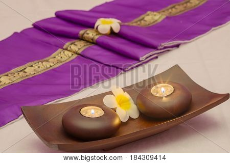 Asian brocade sash, flowers candlesticks with candles on couch