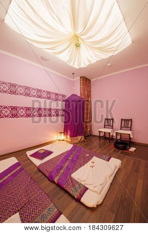 Empty pink cozy room with mats for thai massage and canopy top
