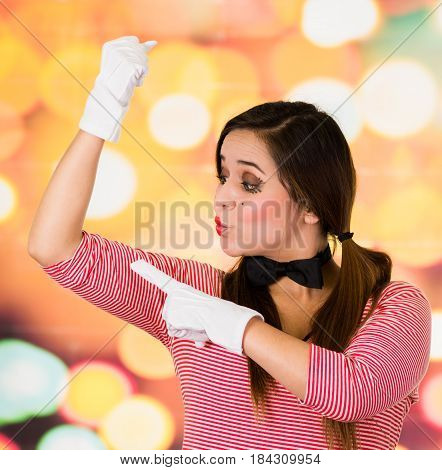 Closeup portrait of female clown mime pointing to upper arm expressing strength
