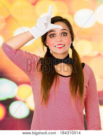 Closeup portrait of female clown mime gesturing loser with fingers over forehead