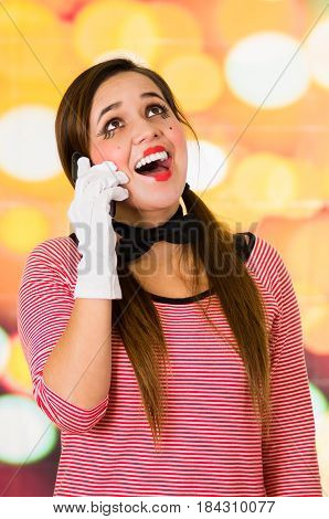 Closeup portrait of cute young girl clown mime using cell phone looking happy