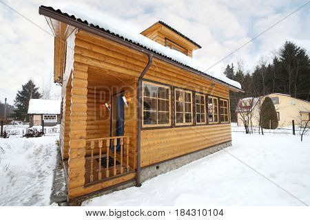 Cozy wooden country house among snow at winter day with snowfall