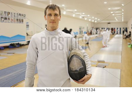 Man in costume with helmet stands in gym for fencing training, other people out of focus