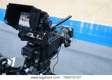 Professional camera with microphone at basketball game in modern stadium