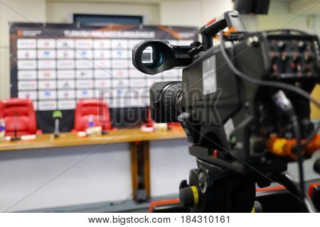 Professional modern camera in empty conference hall, shallow dof