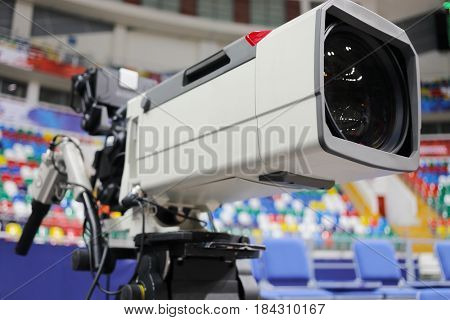 Professional camera at basketball game in modern stadium, shallow dof