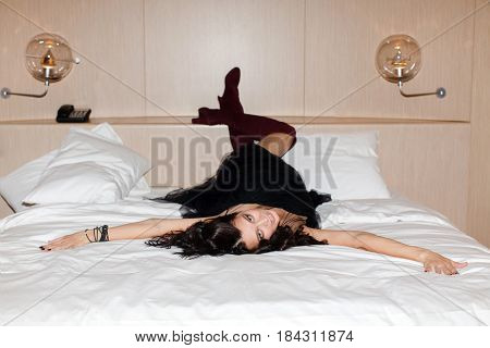 Drunk cheerful woman lying on the bed. Horizontal indoors shot.