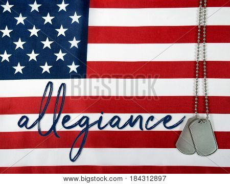 word allegiance and military dog tags on American flag