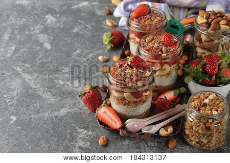 Dietary dessert with chia seeds muesli and strawberries on a gray background