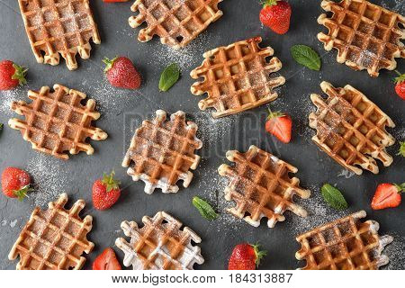 Sweet waffles with strawberries and powdered sugar
