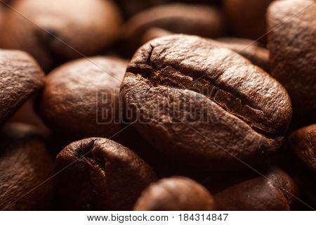 Brown roasted coffee beans in dark close-up macro photo natural food background selective focue shallow depth of field.