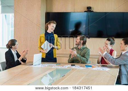 Business team applauding their colleague in conference room at office