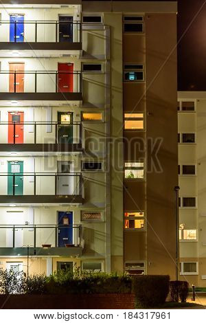 Appartment building with multi color doors at night.