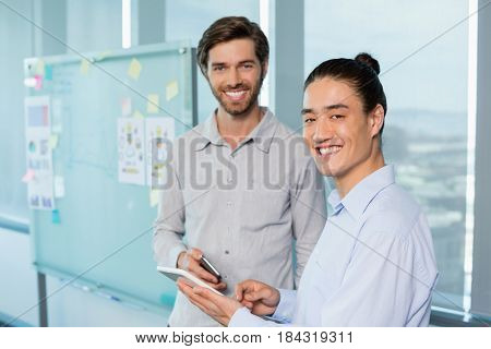 Portrait of business executives discussing over digital tablet at office
