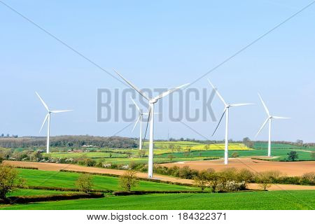 Wind Turbines and Blue Sky with Clouds over UK fields.