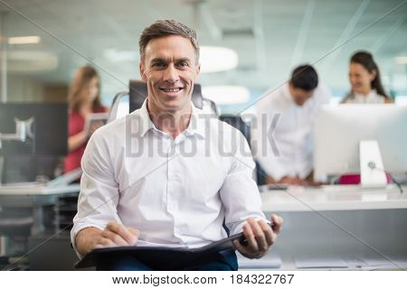 Portrait of smiling business executive sitting on chair and writing on clipboard in office