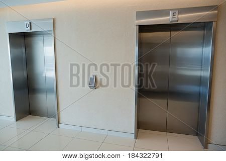 Two modern elevator doors in lobby of office building