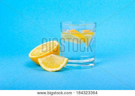 Glass of water with lemon in the morning on a blue background