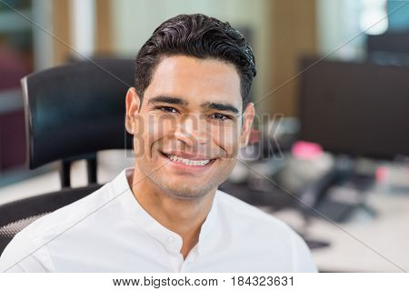 Portrait of smiling business executive sitting on chair in office