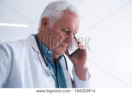 Doctor talking on his mobile phone in the passageway at hospital