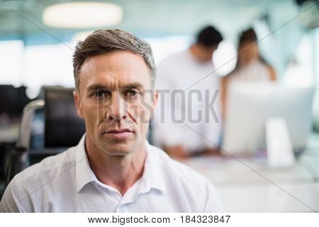 Portrait of serious business executive sitting on chair in office