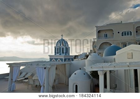 Bell tower and blue dome of a church under dramatic sky at sunset, Imerovigli village, Santorini island, Greece