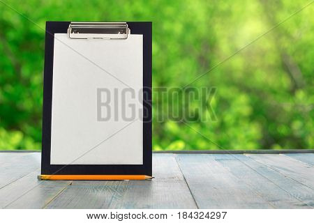 Black clipboard with pencil on a blue wooden table against the background blur green leaves bokeh
