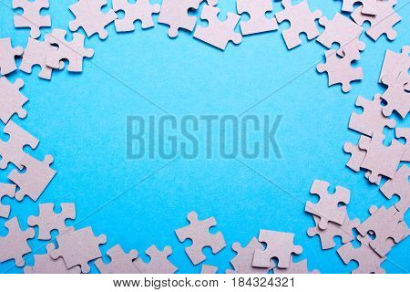Puzzle pieces frame with empty space for text on a blue background