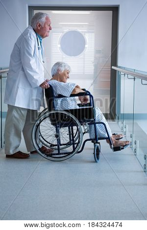 Doctor and senior patient on wheelchair in the passageway at hospital