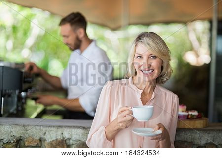 Portrait of woman holding coffee cup in a restaurant