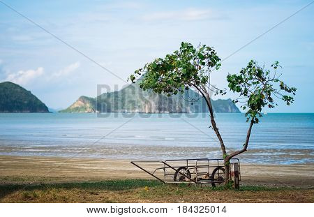 Wooden cart in the tropical paradise outdoor landscape of beautiful secret sea beach with gorgeous water and mountains on horizon in Khao Sam Roi Yot National Park, Thailand.