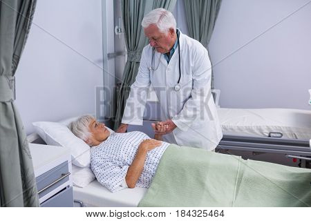 Doctor consoling senior patient in hospital