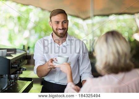 Waiter giving coffee to customer at restaurant