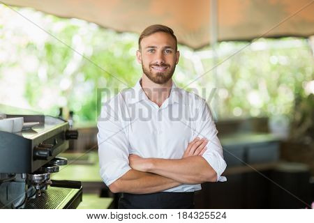 Portrait of waiter standing with arms crossed at restaurant