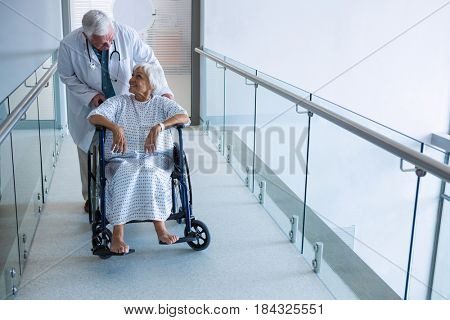 Doctor holding senior patient on wheelchair in passageway at hospital