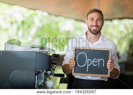 Portrait of waiter holding a board with open sign at restaurant