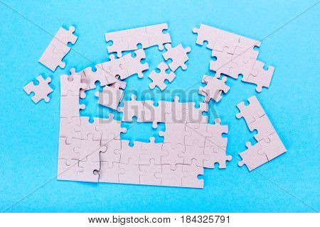 Broken white puzzle on pieces on a blue background