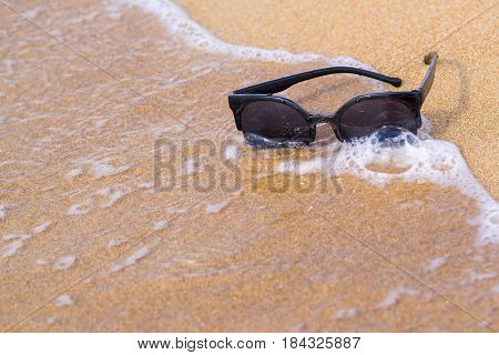 one sunglasses of black color are located separately a closeup on the sandy coast with a sea wave
