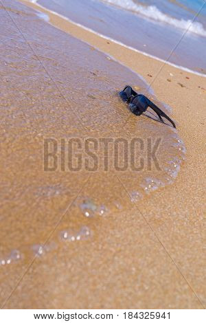 natural background and one black sunglasses with water of a sea wave on the sandy beach of the resort