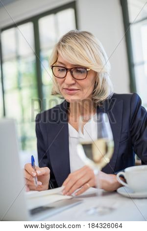 Attentive businesswoman writing on diary in a restaurant