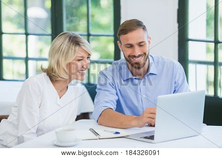 Executives discussing over laptop in a restaurant