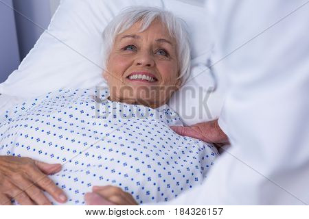 Mid-section of doctor consoling senior patient in hospital