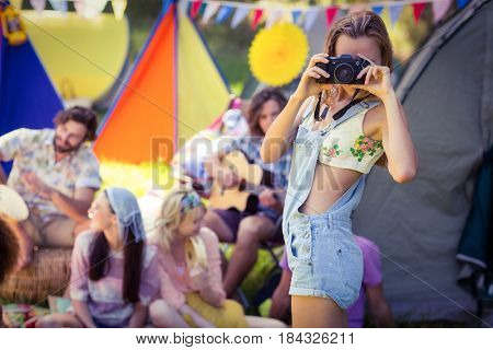 Woman taking a picture at campsite on a sunny day