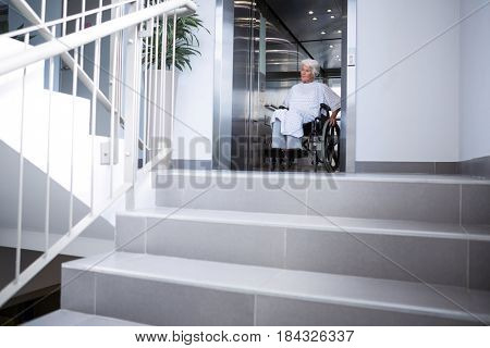 Disabled senior patient on wheelchair in lift at hospital