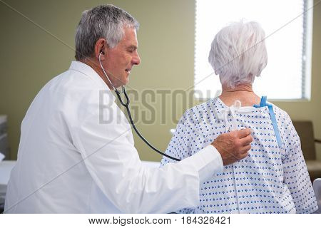 Doctor examining senior patient with stethoscope in hospital