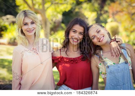 Portrait of smiling friends standing together with arm around in park on a sunny day