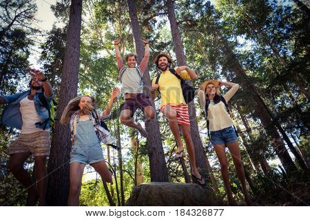 Happy friends having fun in forest on a sunny day