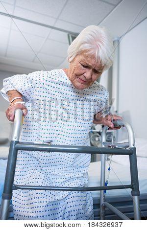 Smiling senior patient holding walking frame to get up at hospital