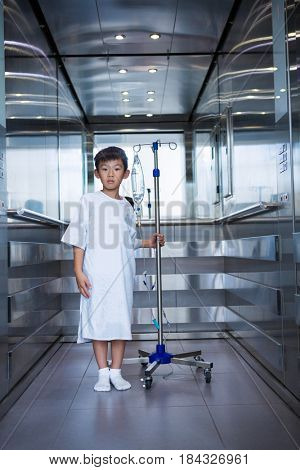 Smiling boy patient holding intravenous iv drip stand in lift at hospital