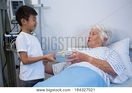 Boy giving a gift to senior patient on bed at hospital